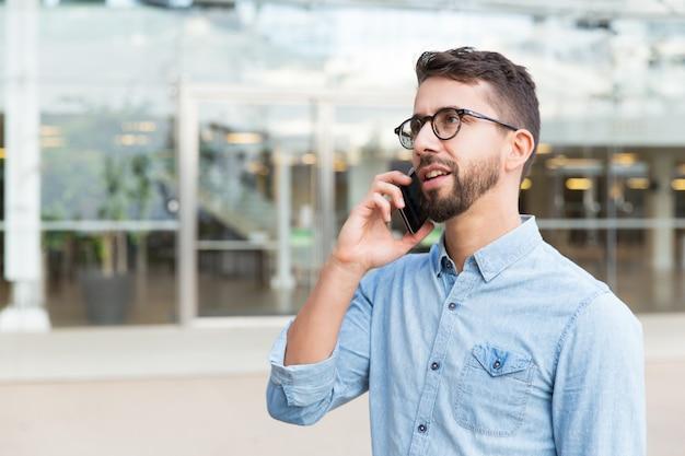 Nachdenklicher kerl im eyewear, der über mobiltelefon spricht