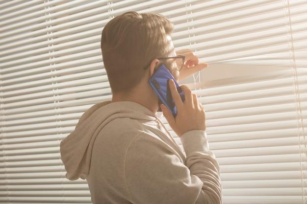 Nachdenklicher kerl spricht auf seinem smartphone und schaut zu hause auf das fenster. männliches denken, träumen und blick aus dem fenster.