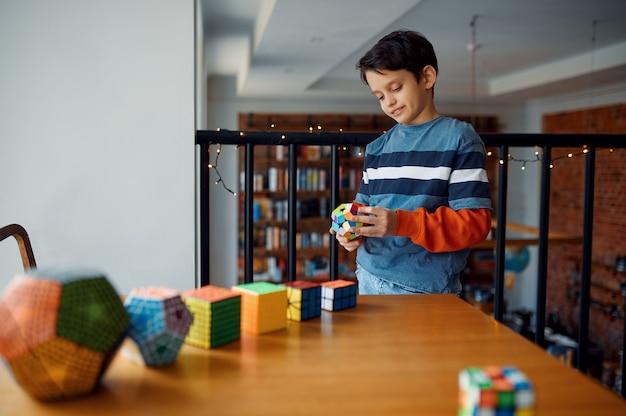 Nachdenklicher kleiner junge spielt mit puzzlewürfeln. spielzeug für gehirn- und logisches denktraining, kreatives spiel, lösung komplexer probleme