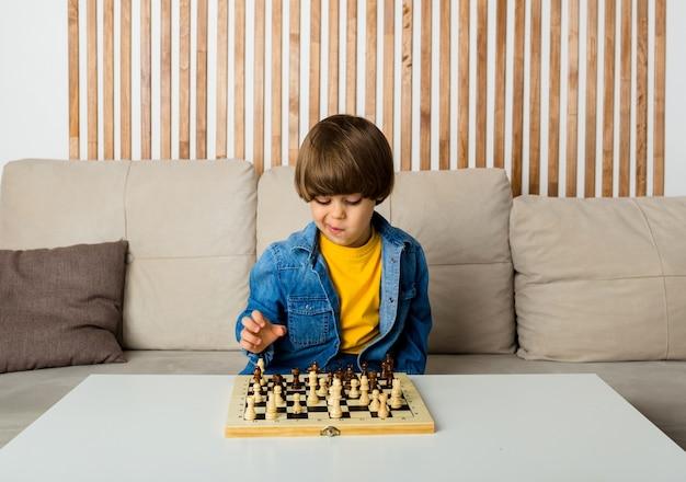 Nachdenklicher kleiner kaukasischer junge mit braunen haaren sitzt auf einem sofa und spielt schach. entwicklung des kindes