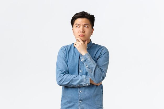 Nachdenklicher komplizierter asiatischer mann im hemd, der das kinn berührt und die obere linke ecke betrachtet, nachdenkt, eine entscheidung trifft, etwas wählt, zweifel hat, zögerlich auf weißem hintergrund steht.