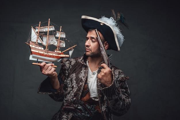 Nachdenklicher korsar mit hut und jacke, der wie ein winziges spielzeugschiff aussieht und eine pistole um den kopf hält.
