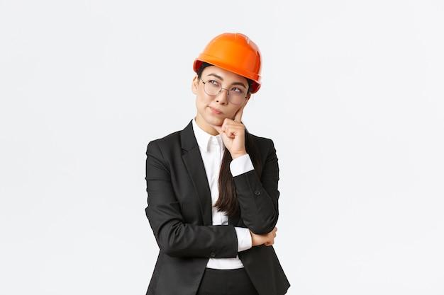Nachdenklicher kreativer weiblicher asiatischer chefarchitekt bauingenieur, der das tragen des schutzhelms und des anzugs denkt, die beste wahl für das bauen der stehenden weißen wand überlegen