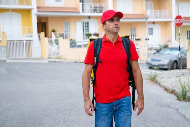 Nachdenklicher kurier, der bestellung liefert und im expressdienst arbeitet. nachdenklicher lieferbote, der rote mütze und hemd trägt, gelben rucksack trägt und geht. lieferservice und online-shopping-konzept