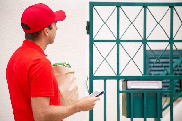 Nachdenklicher kurier stehend und adresse per tablet in der hand überprüfend. nachdenklicher lieferbote, der lebensmittel in papiertüte liefert und rotes hemd und kappe trägt. lieferservice und online-shopping-konzept