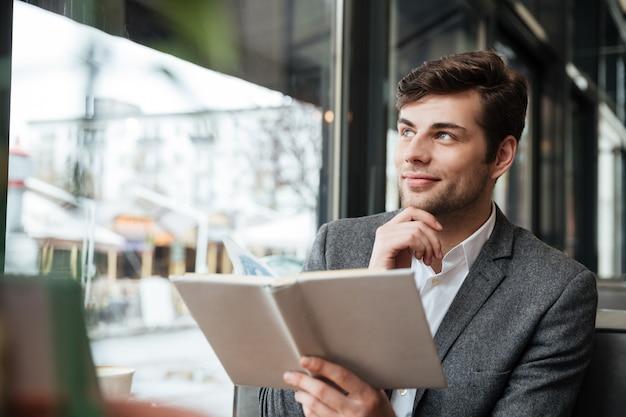 Nachdenklicher lächelnder geschäftsmann, der durch die tabelle im café mit laptop-computer beim halten des buches und weg schauen sitzt