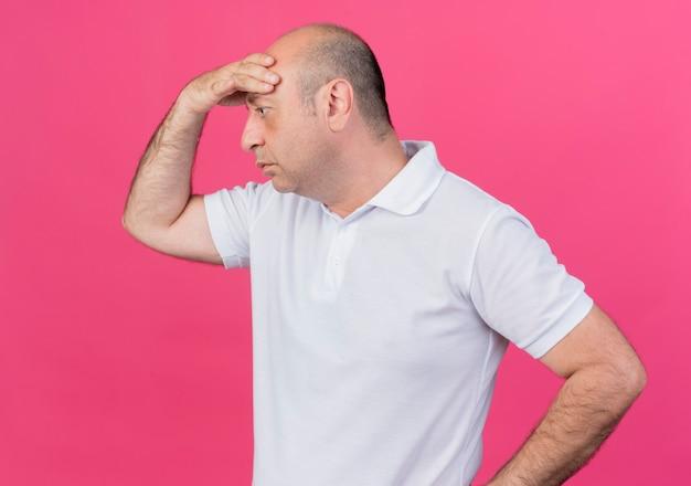 Nachdenklicher lässiger reifer geschäftsmann, der hand auf stirn setzt, die gerade lokalisiert auf rosa hintergrund schaut