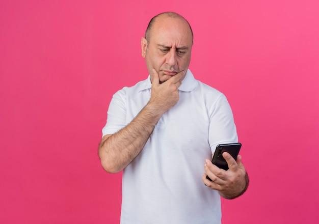 Nachdenklicher lässiger reifer geschäftsmann, der handy hält und betrachtet und hand auf kinn lokalisiert auf rosa hintergrund mit kopienraum hält