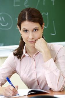 Nachdenklicher lehrer schriftlich in ihrem notizbuch
