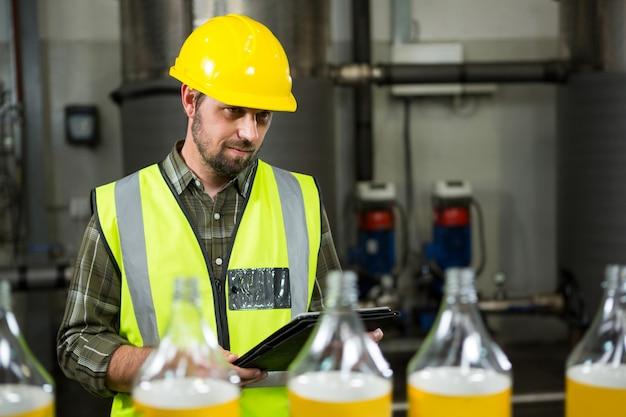 Nachdenklicher männlicher arbeiter mit digitalem tablett in der fabrik