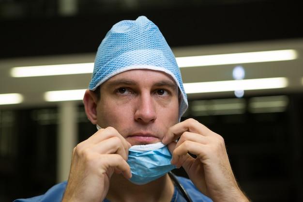 Nachdenklicher männlicher chirurg, der chirurgische maske trägt