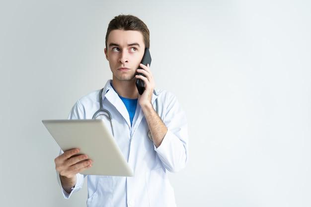 Nachdenklicher männlicher doktor, der tablet-computer und smartphone verwendet