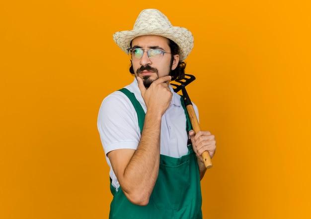 Nachdenklicher männlicher gärtner in der optischen brille, die gartenhut trägt, legt hand auf kinn und hält rechen, der zur seite schaut