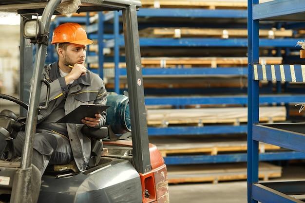 Nachdenklicher männlicher ingenieur, der schutzuniform und einen sitzenden helm trägt