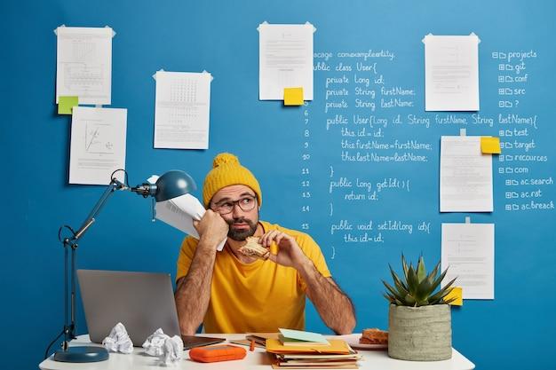 Nachdenklicher männlicher programmierer oder softwareentwickler denkt über programmcode nach, schaut weg und isst burger, hält papiere, trägt gelbe kleidung und verbringt zeit für die erstellung eines projekts.