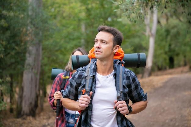 Nachdenklicher männlicher rucksacktourist, der natur betrachtet und mit langhaariger frau wandert. glückliches kaukasisches junges paar, das im wald geht. backpacking tourismus, abenteuer und sommerurlaub konzept