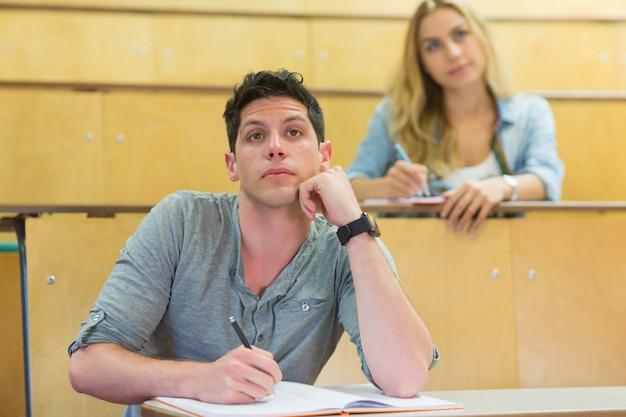 Nachdenklicher männlicher student während des unterrichts im hörsaal