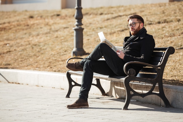 Nachdenklicher mann, der auf bank sitzt und zeitung draußen liest