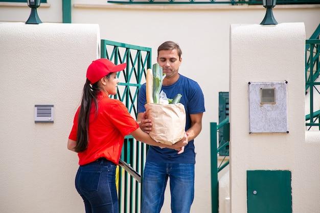 Nachdenklicher mann, der bestellung vom lebensmittelgeschäft erhält und draußen steht. lateinischer professioneller weiblicher kurier in der roten uniform, die gemüse vom lebensmittelgeschäft liefert. lebensmittel-lieferservice und post-konzept