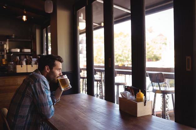 Nachdenklicher mann, der bier trinkt