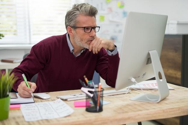 Nachdenklicher mann, der hart am computer arbeitet
