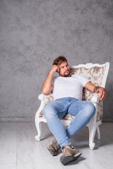 Nachdenklicher mann, der im lehnsessel sitzt