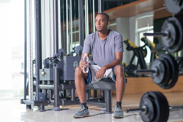 Nachdenklicher mann, der in der turnhalle, wasserflasche halten sitzt