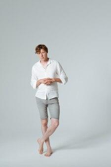 Nachdenklicher mann, der in voller länge verschränkte arme und gekreuzte beine steht. denken barfuß männliches modell in weiß