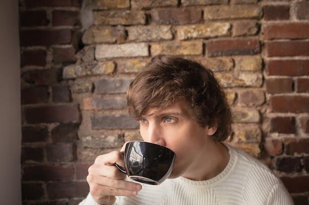 Nachdenklicher mann, der kaffee trinkt