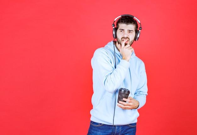 Nachdenklicher mann, der kaffeetasse hält und musik hört
