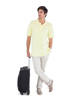 Nachdenklicher mann, der mit seinem koffer steht