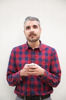 Nachdenklicher mann, der smartphone hält und oben schaut