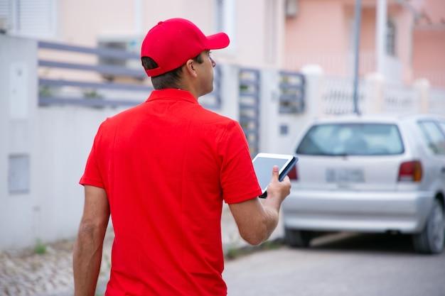 Nachdenklicher mann, der tablette hält, steht und adresse sucht. kaukasischer professioneller kurier in der roten uniform, die auf straße geht.