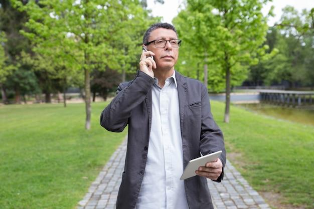 Nachdenklicher mann, der tablette verwendet und um telefon im park ersucht