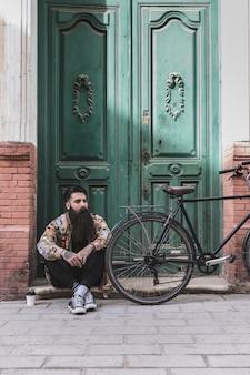 Nachdenklicher mann, der vor alter tür mit seinem fahrrad sitzt