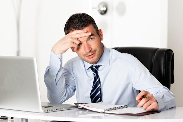 Nachdenklicher mann im büro mit computer und stift