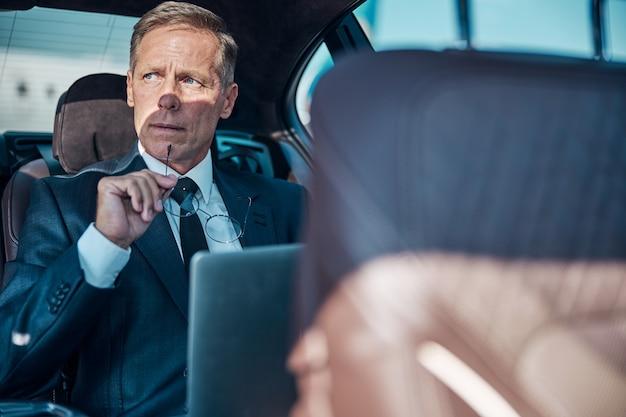 Nachdenklicher mann im eleganten anzug sitzt hinten im auto und benutzt laptop nach der landung mit dem flugzeug laptop