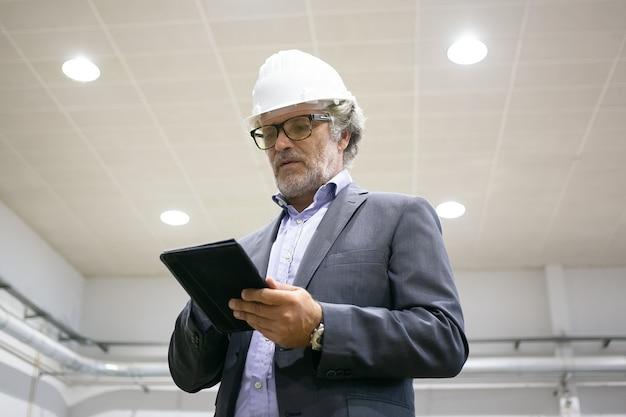 Nachdenklicher mann im schutzhelm, der tablette hält und bildschirm betrachtet