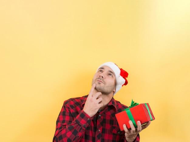 Nachdenklicher mann in einem roten hut, hält ein geschenk mit interesse auf seinem gesicht