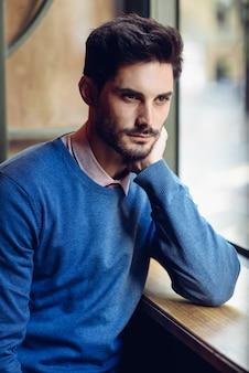 Nachdenklicher mann mit blauer strickjacke mit verlorenem blick nahe einem fenster
