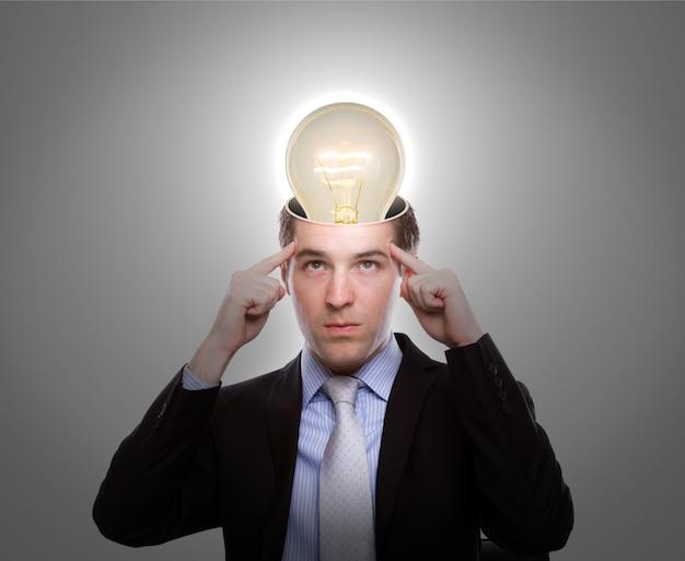 Nachdenklicher mann mit einer glühbirne auf dem kopf