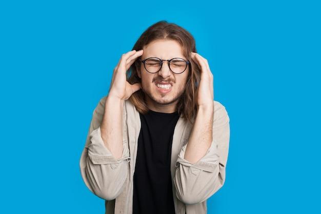 Nachdenklicher mann mit langen haaren und brille berührt seinen kopf beim posieren