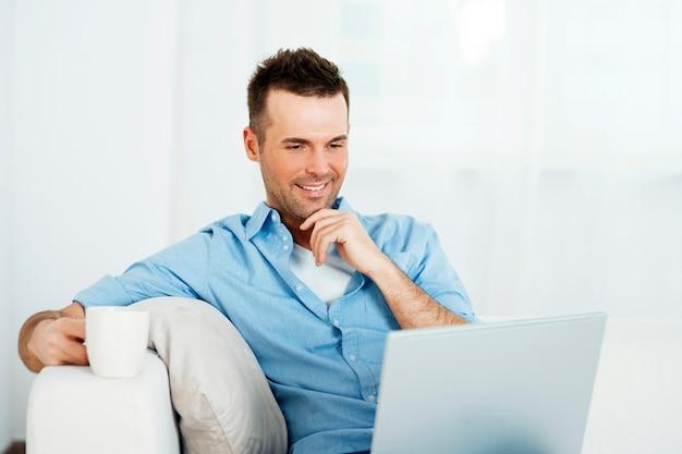 Nachdenklicher mann mit laptop und tasse kaffee