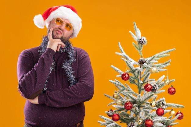 Nachdenklicher mann mittleren alters, der weihnachtsmütze und lametta-girlande um den hals mit gläsern trägt, die nahe geschmücktem weihnachtsbaum stehen