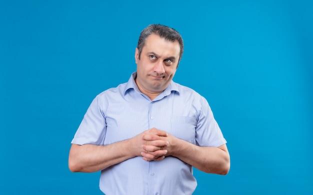 Nachdenklicher mann mittleren alters im blau gestreiften hemd, der seine hände auf einem blauen hintergrund zusammendenkt und reibt