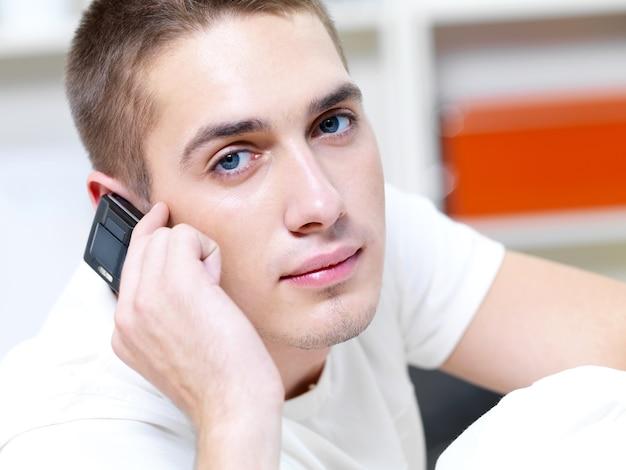 Nachdenklicher mann ruft im telefon auf weiß an