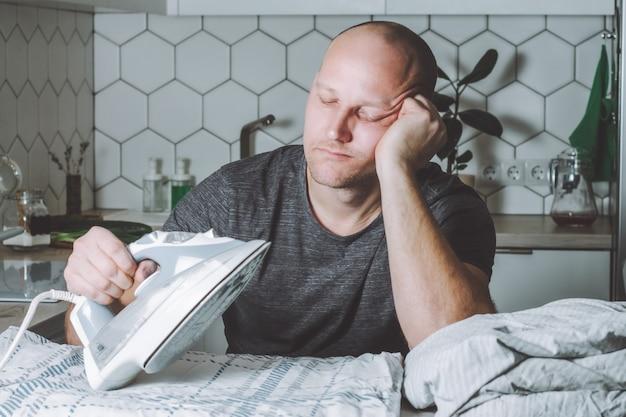 Nachdenklicher mann schaut auf eisen und bettwäsche vater ist mit hausarbeiten beschäftigt