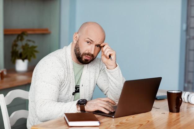 Nachdenklicher mann tippt auf einem laptop, arbeitet zu hause, arbeitet online, coronavirus