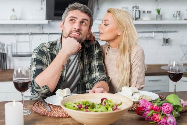 Nachdenklicher mann und blonde frau, die am tisch in der küche sitzen