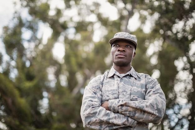 Nachdenklicher militärsoldat, der mit verschränkten armen im bootcamp steht